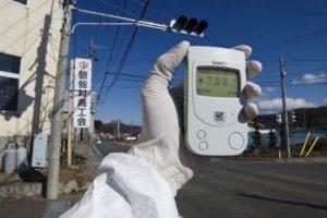 267794-photo-fournie-par-greenpeace-de-l-un-de-ses-membres-mesurant-a-l-aide-d-un-compteur-geiger-la-radioa