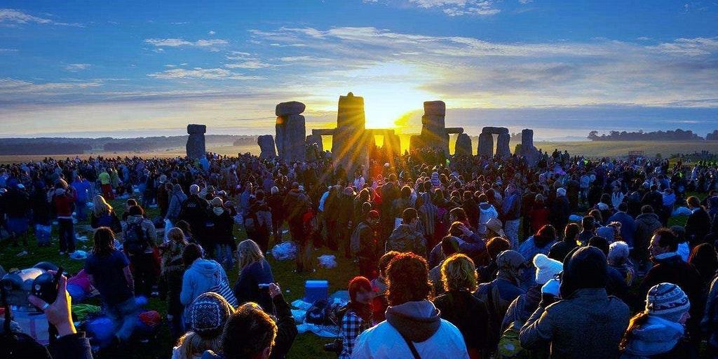 Les fêtards regardent le Solstice Sun s'élever sur Stonehenge Heel Stone